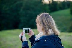 Donna che prende le immagini con la sua macchina fotografica del telefono fotografia stock