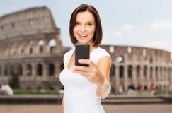 Donna che prende selfie con lo smartphone sopra il Colosseo Fotografie Stock Libere da Diritti