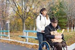 Donna che prende un acquisto di drogheria disabile dell'uomo Immagine Stock