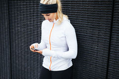 Donna che prende un allenamento della forma della rottura facendo uso del telefono cellulare Immagine Stock