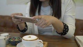 Donna che prende un'immagine del suo cappuccino con uno smartphone stock footage