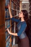Donna che prende un libro dallo scaffale per libri Immagini Stock Libere da Diritti