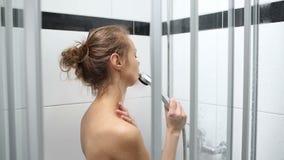 Donna che prende una doccia stock footage