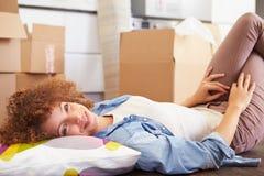 Donna che prende una rottura mentre muovendosi nella nuova casa Immagine Stock