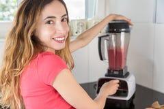 Donna che prepara frullato sano con una macchina Fotografia Stock