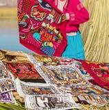 Donna che prepara i ricordi in Uros, Perù, Bolivia. Immagine Stock