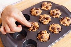 Donna che prepara il muffin di pepita di cioccolato di cottura Fotografie Stock Libere da Diritti