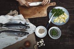 Donna che prepara il pesce dello sgombro immagini stock libere da diritti