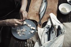 Donna che prepara il pesce dello sgombro Fotografia Stock