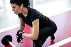 Donna che prepara per il suo allenamento di sollevamento pesi con il piccolo bilanciere Immagine Stock Libera da Diritti