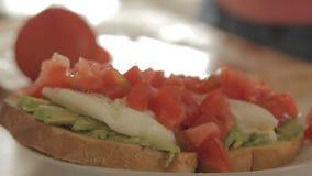 Donna che prepara prima colazione sana con l'avocado su pane, sulle uova e sul pomodoro arrostiti video d archivio