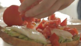 Donna che prepara prima colazione sana con l'avocado su pane, sulle uova e sul pomodoro arrostiti stock footage