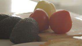 Donna che prepara prima colazione sana con l'avocado su pane, sulle uova e sul pomodoro arrostiti archivi video