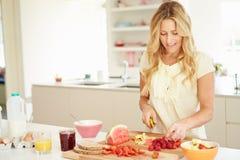 Donna che prepara prima colazione sana in cucina Fotografia Stock Libera da Diritti