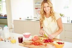 Donna che prepara prima colazione sana in cucina Fotografie Stock