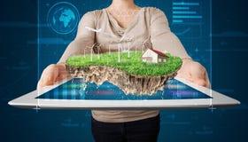 Donna che presenta una terra perfetta di ecologia con una casa e un windmil Fotografia Stock Libera da Diritti
