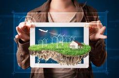 Donna che presenta una terra perfetta di ecologia con una casa e un windmil Immagini Stock Libere da Diritti