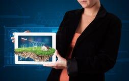 Donna che presenta una terra perfetta di ecologia con una casa e un windmil Fotografia Stock