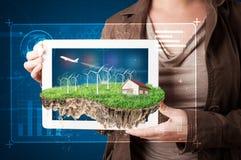Donna che presenta una terra perfetta di ecologia con una casa e un windmil Immagine Stock Libera da Diritti