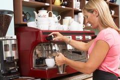 Donna che produce caffè in caffè Fotografie Stock Libere da Diritti