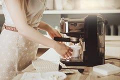 Donna che produce caffè espresso fresco in macchinetta del caffè la macchina del caffè fa Immagini Stock