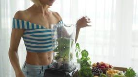 Donna che produce frullato di verdure verde con il miscelatore Stile di vita sano di cibo archivi video