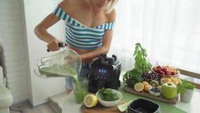 Donna che produce frullato di verdure verde con il miscelatore Stile di vita sano di cibo video d archivio