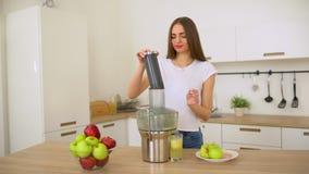 Donna che produce il succo di mele sugli spremiagrumi e che lo beve fresco a casa in cucina Juicing e donna felice mangiante in b video d archivio