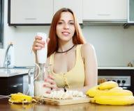 Donna che produce le bevande dalle banane e dal latte Fotografia Stock Libera da Diritti
