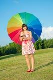 Donna che propone sulla natura con l'ombrello di colore Immagine Stock