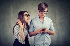 Donna che prova a portare attenzione di un uomo bello che la trascura facendo uso di uno smartphone immagini stock