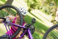 Donna che prova a riparare catena sul mountain bike in parco Fotografia Stock Libera da Diritti