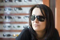 Donna che prova sugli occhiali da sole Immagini Stock