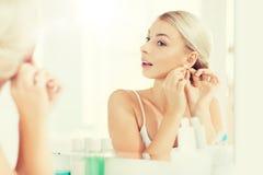 Donna che prova sull'orecchino che esamina lo specchio del bagno immagini stock libere da diritti