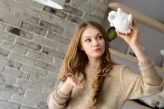 Donna che prova a trovare più soldi nel porcellino salvadanaio Fotografia Stock