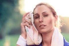 Donna che pulisce fronte con l'asciugamano dopo l'esercizio Fotografie Stock Libere da Diritti