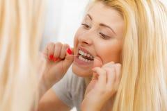 Donna che pulisce i suoi denti facendo uso del filo per i denti immagine stock libera da diritti