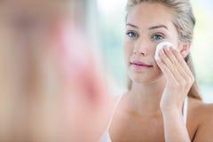 Donna che pulisce il suo fronte con il cuscinetto di cotone Immagine Stock Libera da Diritti