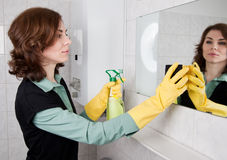 Donna che pulisce la stanza da bagno Immagine Stock
