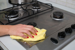 Donna che pulisce la superficie del gas dell'acciaio inossidabile nella cucina alla h immagini stock