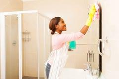Donna che pulisce lo specchio del bagno Fotografia Stock Libera da Diritti
