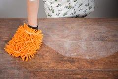 Donna che pulisce tavola polverosa Fotografia Stock Libera da Diritti