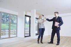 Donna che raccoglie le chiavi alla nuova casa dall'agente immobiliare immagini stock