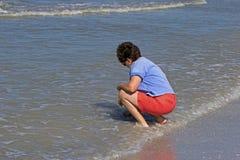 Donna che raccoglie le coperture nella spuma nel golfo del Messico Immagini Stock