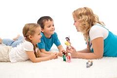 Donna che racconta una storia ai suoi bambini sul pavimento Immagine Stock