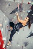 Donna che raggiunge la cima della parete bouldering artificiale mentre esercitandosi nella palestra Fotografia Stock