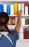 Donna che raggiunge nella dispensa Fotografie Stock Libere da Diritti