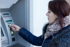 Donna che recupera la sua carta assegni al BANCOMAT Fotografie Stock Libere da Diritti