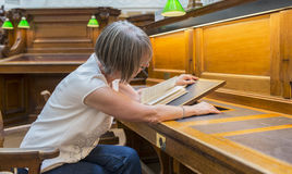 Donna che regola il supporto di libro in biblioteca Fotografia Stock Libera da Diritti