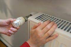 Donna che regola termostato Immagine Stock